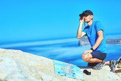 Traveler with map and Spyglass on the cliff. Male traveler with map and Spyglass standing on the trail on the cliff against sea and blue sky at early morning Stock Images