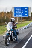 Traveler with motorbike standing on roadside in front of direction board. The Kola route from Murmansk city, Russia Royalty Free Stock Photography