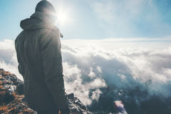 Traveler on mountain summit with sun over clouds Royalty Free Stock Photos