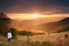 Traveler at mountain sunset background. One girl look at gorgeous sunset in mountains. Beautiful summer evening. Traveler at mountain sunset background. Copy Royalty Free Stock Images
