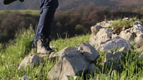 Traveler in mountaineering boots stepping on the stones at mountain landscape stock video