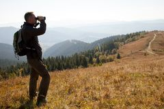 A traveler in the mountains looks in the binoculars. A young man stands on a mountain ridge, looking in the binoculars, in search of adventure stock photos