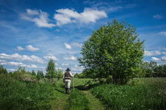 Traveler in old clothes with a knapsack. On an abandoned country road Stock Image