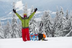 Traveler with open arms stands on the background of huge pine tr. Ees covered with snow, next to equipment for winter travel. Epic winter adventure in the stock images
