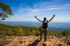 Traveler with open arms stands on the cliff, among green hills royalty free stock images