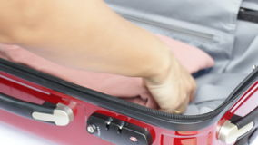 Traveler opening suitcase for packing the cloth stock footage