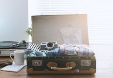 Traveler packing his suitcase before leaving. Traveler packing his luggage before leaving for a vacation: open vintage suitcase with clothes, camera and vintage Royalty Free Stock Photo