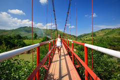 Traveler passes the river on a suspension bridge. Vietnam Royalty Free Stock Image