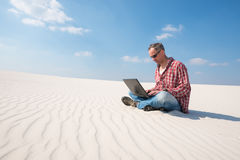 Traveler is passionate about work, with a laptop. On his lap sits in the middle of the desert. Concept - freelance your work, your life Royalty Free Stock Photography