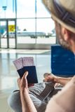 Traveler with passports and tickets. Waiting for someone in airport Royalty Free Stock Image