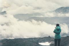 Traveler with photo camera enjoy cloudy foggy mountains Royalty Free Stock Image