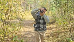 Traveler photographing scenic views in forest by mountain river. Man shooting picturesque views. Guy takes photo and. Traveler photographing scenic views in stock video