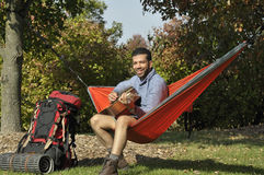 Traveler Playing Guitar in a Hammock Stock Image