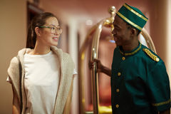 Traveler and porter. Hospitable porter talking to young tourist in aisle of hotel Royalty Free Stock Image