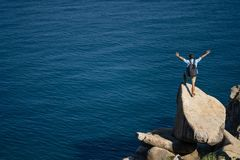 Traveler posing on stone on rocky seashore outdoors stock photo