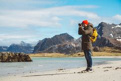 Traveler is a professional photographer taking over the landscape photo landscape. Wearing a yellow backpack in a red. Hat standing on a sandy beach on the stock photo