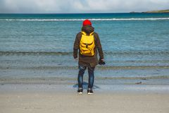 Traveler is a professional photographer taking over the landscape photo landscape. Wearing a yellow backpack in a red. Hat standing on a sandy beach on the stock image