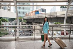 Traveler pull luggage and shopping in city. Asian beauty young woman traveler walking, pulling luggage, carrying merchant bags in modern city with sky train and Royalty Free Stock Photo
