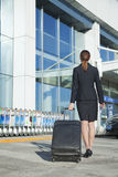Traveler pulling suitcase into airport Stock Photo
