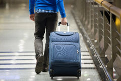 Traveler pulling suitcase close-up. Young man pulling suitcase in modern airport terminal. Travelling guy wearing smart casual style clothes walking away with Royalty Free Stock Image