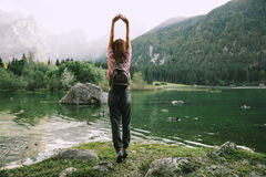Traveler with raised arms up on the nature. With Lago di Fusine lake with Mangart mountains in the background. Travel, Freedom, Lifestyle concept. Udine, Italy Royalty Free Stock Photography