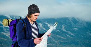 Traveler reading map while carrying backpack on mountain. Digital composite of Traveler reading map while carrying backpack on mountain Stock Images