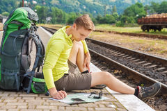 Traveler reading a map. Man sitting with map and travel bag at the train station. Traveler holding map, waiting for a train at train station and planing for next Stock Photos
