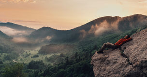 Traveler resting on top of cliff Stock Photo