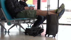 Traveler rests his feet on his luggage. A typical scene at an airport or mass transit terminal stock footage