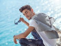 Man traveler near the sea. Traveler on the rocks near the sea looking at camera. Summer Travel Vacation. Smiling handsome young caucasian tourist man in casual Stock Image