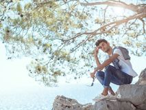 Man traveler near the sea. Traveler on the rocks near the sea under a tree looking at camera. Summer Travel Vacation. e view of handsome young caucasian tourist Stock Photo