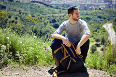 Traveler with rucksack resting on a halt on a mountain trail and looking away Stock Photos