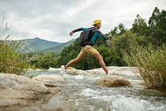 Traveler running through shallow rocky river on nature background stock photo