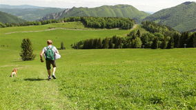 A traveler runs down into a green valley competing with his pet beagle.  stock footage