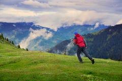 Traveler runs through the green alpine meadow Stock Photos