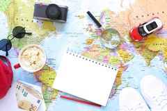 Traveler`s accessories and items with copy space on world map background, travel by car concept. Horizontal. Top view royalty free stock photography