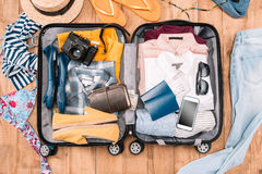 Traveler`s accessories organized in open luggage on wooden floor Stock Photos
