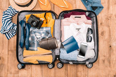 Traveler`s accessories organized in open luggage on wooden floor Royalty Free Stock Photo