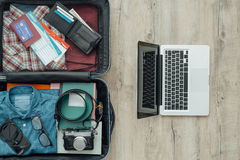 Traveler's bag. Open traveler's bag on a desktop with clothing, accessories, credit card, tickets and passport, travel and vacations concept Stock Photography