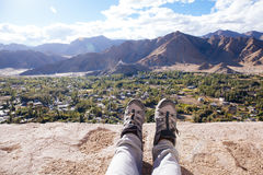 Traveler`s boots relaxing and resting his feet on high mountain trekking and ancient town scene and adventure Stock Images