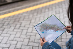 Traveler's hands holding map at train station platform, with copy space Royalty Free Stock Photography