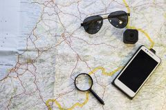Traveler's items on a map. Aviator sunglasses, magnifying glass, an action camera and a mobile phone. Travel or camping concept. Space for your text or image Royalty Free Stock Photos