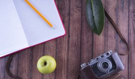 Traveler`s notes. Set for rest and travel. Desktop adventurer. Old camera, pencil notebook and Apple-healthy food concept stock photo
