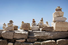 Traveler's Rock Piles. Closeup of a series of rock piles built by travelers to bring them good luck. Background is the birght blue sky with a hint of the Royalty Free Stock Image