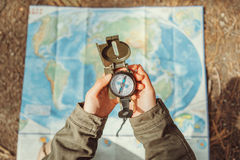 Traveler searching direction with a compass on background of map Royalty Free Stock Photography