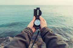 Traveler searching direction with a compass on coast Stock Image