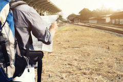 Traveler searching right direction on map. Royalty Free Stock Images