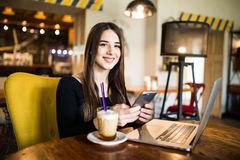 Traveler sending emails with laptop and smartphone during coffee break indoor Stock Photography