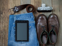 Traveler set with a digitizer, leather belt, rangefinder camera,. Jeans and boots on old boards of table Stock Photography