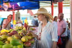 Traveler shopping on traditional Victoria food market, Seychelles. Female traveler wearing elegant colonial style white tunic and hat buying fresh tropical stock photography